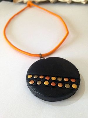 Black round pendant with bronze and copper highlights on orange silk cord