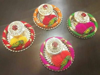 Lovely metal kumkum/coin boxes with colorful gotta bangle base, pompoms & wooden parrot.